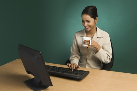 food technology: Businesswoman working in an office with a cup of coffee