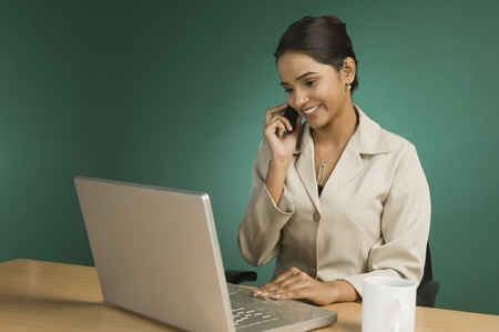 good looking woman: Businesswoman using a laptop and talking on a mobile phone