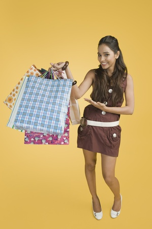 Woman showing shopping bags and smiling Stock Photo - 10168264