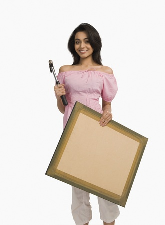 Portrait of a woman holding a hammer and a picture Stock Photo - 10166848