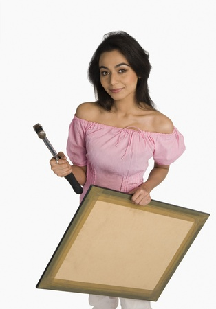 Portrait of a woman holding a hammer and a picture Stock Photo - 10168758