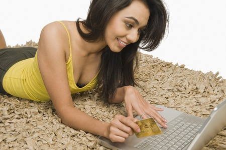 Woman holding a credit card and working on a laptop Stock Photo - 10167970