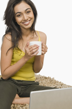 Woman sitting in front of a laptop and holding a cup of coffee Imagens