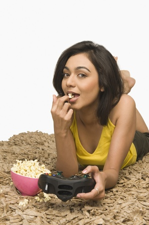 Portrait of a woman eating popcorn and playing video game Stock Photo - 10168206