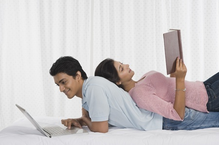 romance: Man using a laptop and his girlfriend lying on his back and reading a book