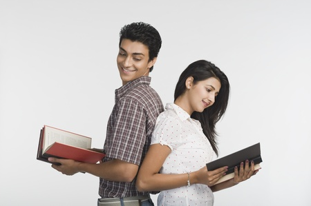 College students standing back to back and reading books Stock Photo - 10167381