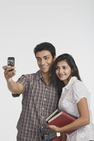 clipping  messaging: College students taking a picture of themselves with a camera mobile