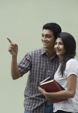 College students holding books and smiling Imagens