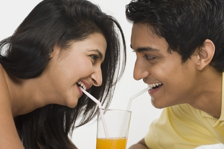 Couple sharing juice from a glass Stock Photo - 10167739