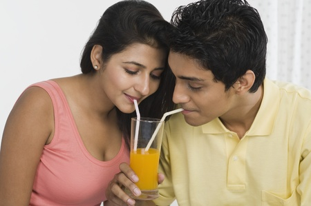 Couple sharing juice from a glass Stock Photo - 10167640