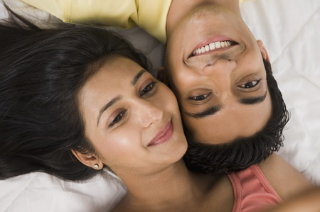 indian couple: Close-up of a couple lying on the bed and smiling