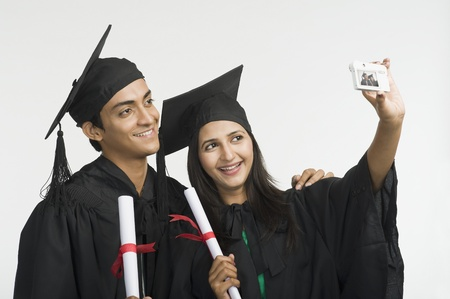 Couple in graduation gown taking a picture of themselves Stock Photo - 10168496