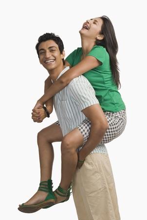 Woman riding piggyback on a man Stock Photo