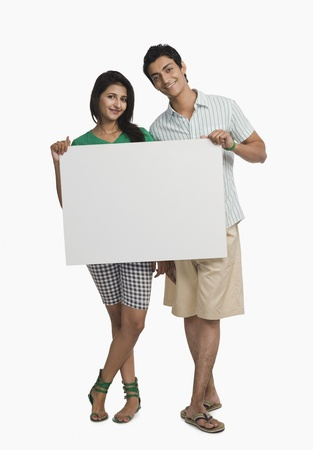 Couple holding a blank placard Imagens