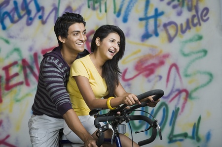 Couple riding a bicycle and smiling Stock Photo - 10167596