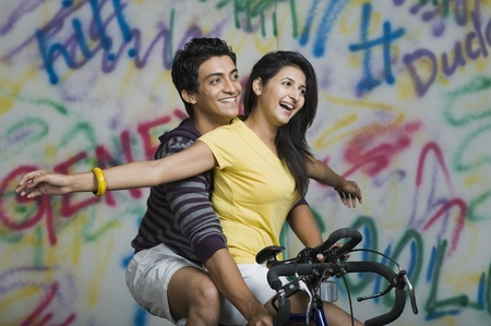 Couple riding a bicycle and smiling Stock Photo - 10167643