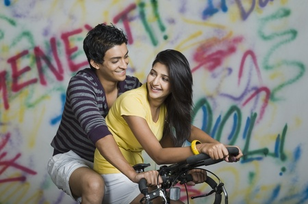 Couple riding a bicycle and smiling Banco de Imagens - 10167610