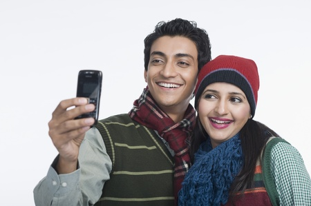 clipping  messaging: Couple taking a picture of themselves with a camera phone