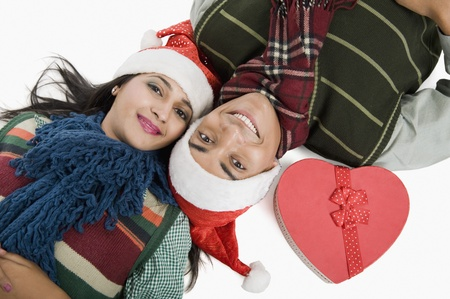 path to romance: Close-up of a couple lying on a floor with Christmas present