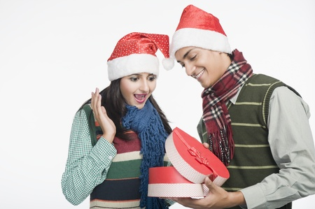 romance: Couple looking at a Christmas present LANG_EVOIMAGES