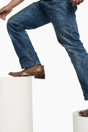 Man in jeans climbing up steps Stock Photo - 10167664
