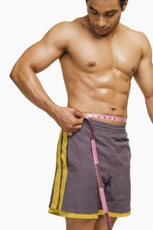 Man measuring his waist Stock Photo - 10168159