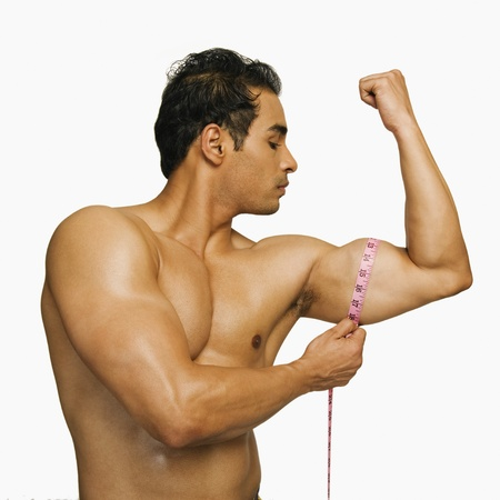 body conscious: Close-up of a man measuring his biceps with a tape measure LANG_EVOIMAGES