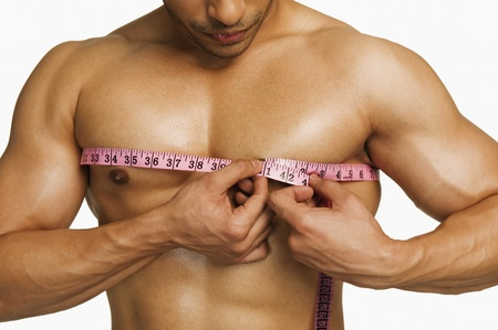 only the biceps: Close-up of a man measuring his chest with a tape measure