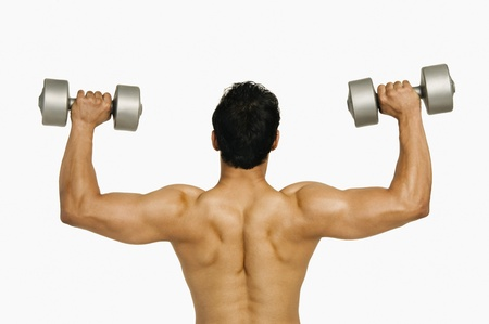 Rear view of a man exercising with dumbbells Stock Photo - 10166982