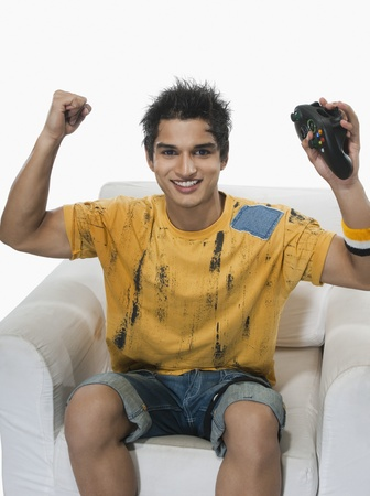 Portrait of a man cheering while playing video game Stock Photo - 10168082