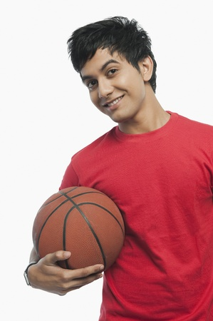 Portrait of a man holding a basket ball and smiling Imagens