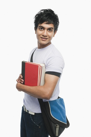 indian subcontinent ethnicity: Portrait of a college student holding notebooks LANG_EVOIMAGES