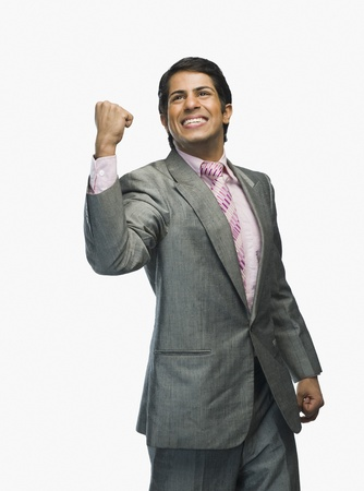 indian subcontinent ethnicity: Businessman clenching fists in excitement