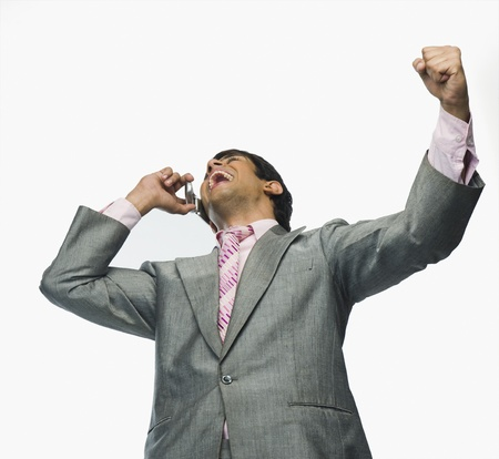 triumphing: Businessman talking on a mobile phone