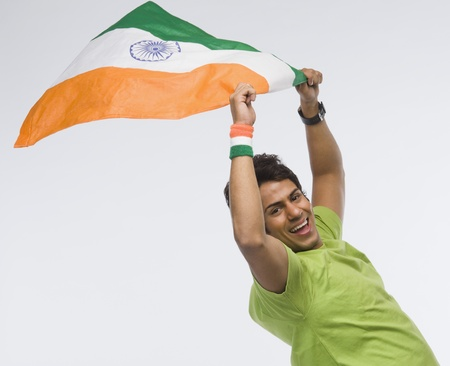 traditionally indian: Portrait of a man holding aloft an Indian flag LANG_EVOIMAGES