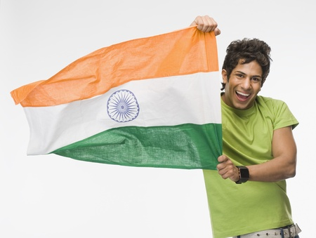 indian subcontinent ethnicity: Portrait of a man holding Indian flag LANG_EVOIMAGES