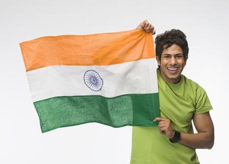 indian subcontinent ethnicity: Portrait of a man holding aloft an Indian flag LANG_EVOIMAGES