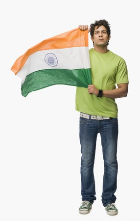 indian subcontinent ethnicity: Man holding an Indian flag LANG_EVOIMAGES
