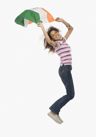 Portrait of a woman jumping with an Indian flag Imagens