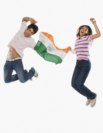 indian subcontinent ethnicity: Couple holding Indian flag and jumping