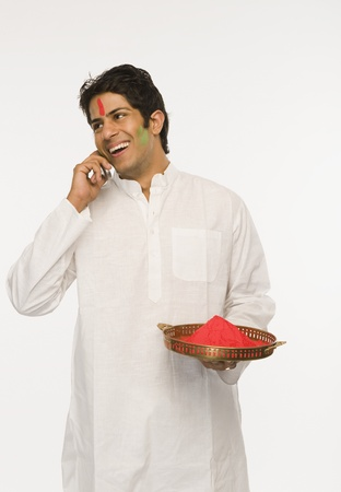 communicatio: Man holding Holi colors and talking on a mobile phone