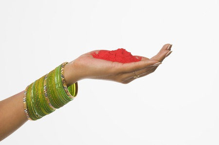 Close-up of a womans hand holding Holi colors