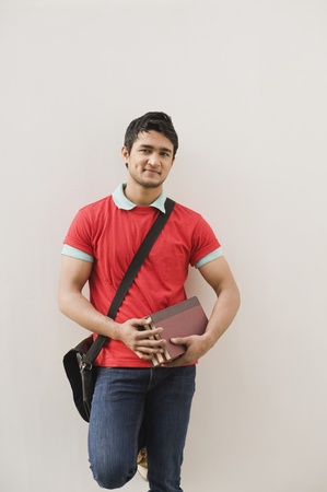 red wall: Man leaning against a wall and holding books