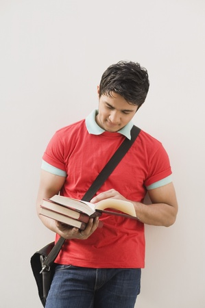 red wall: Man leaning against a wall and reading a book LANG_EVOIMAGES