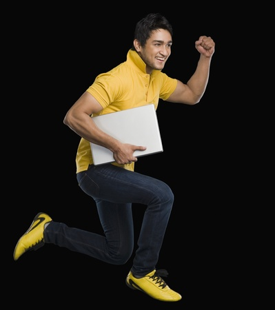 Man carrying a laptop and smiling Stock Photo - 10166815