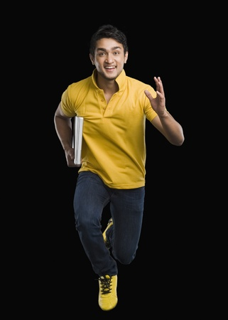 accomplishment: Portrait of a man carrying a laptop and smiling LANG_EVOIMAGES