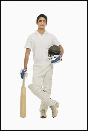 cricketer: Portrait of a cricket batsman standing with a bat and a helmet
