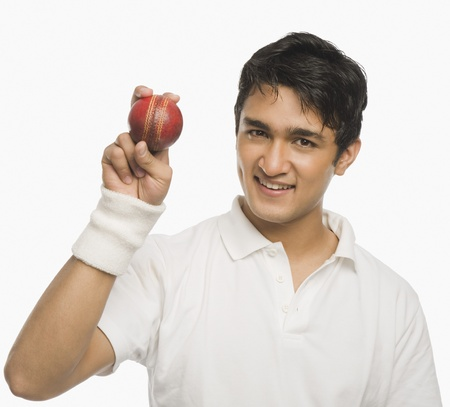 Cricket player showing a cricket ball