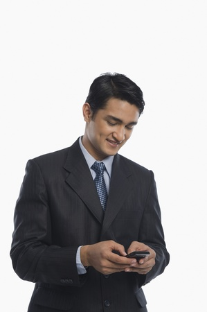 clipping  messaging: Businessman text messaging on a mobile phone LANG_EVOIMAGES