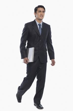 Businessman carrying a laptop Stock Photo - 10166766